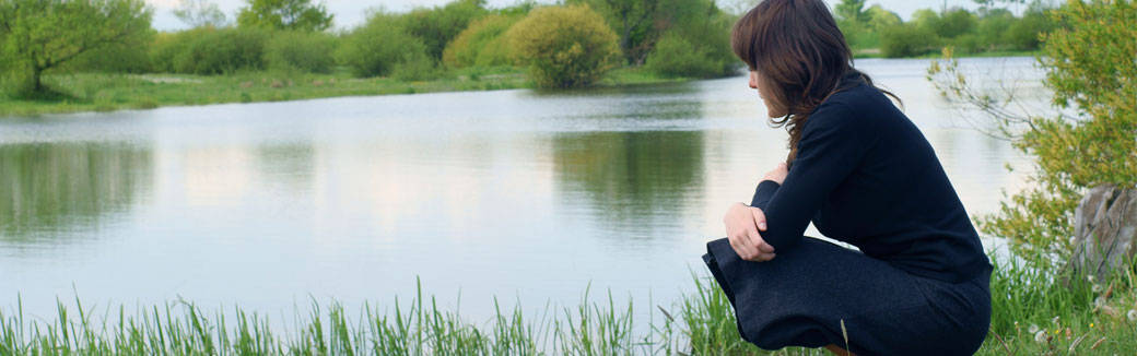 Woman sitting on the shore of a lake, gazing at water.