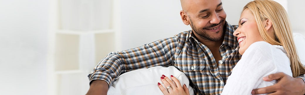couple sitting on couch laughing together