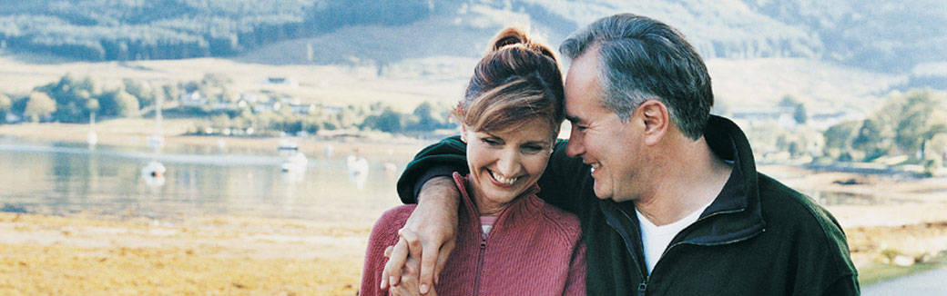 older couple outside, smiling, with heads together