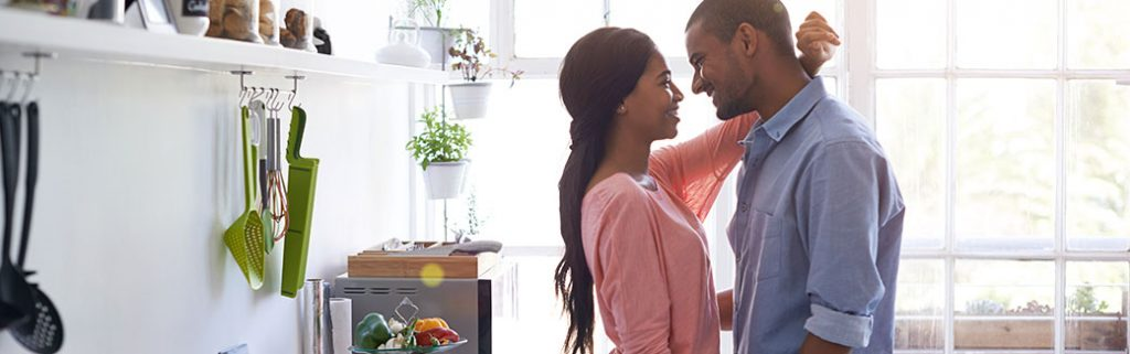 married couple in the kitchen facing each other; wife has arms around husband.