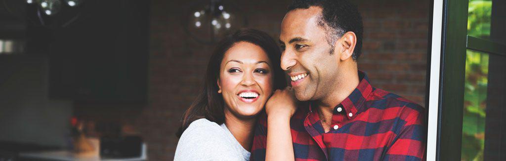 wife on her husbands shoulder, smiling