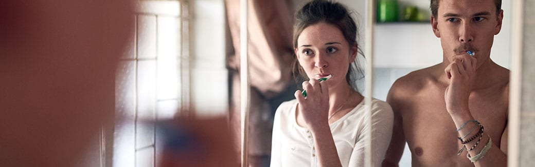 man and woman looking in a mirror brushing their teeth