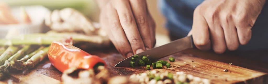 close-up of man chopping green onions