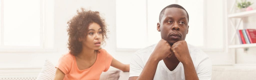 man and woman sitting on the couch looking troubled